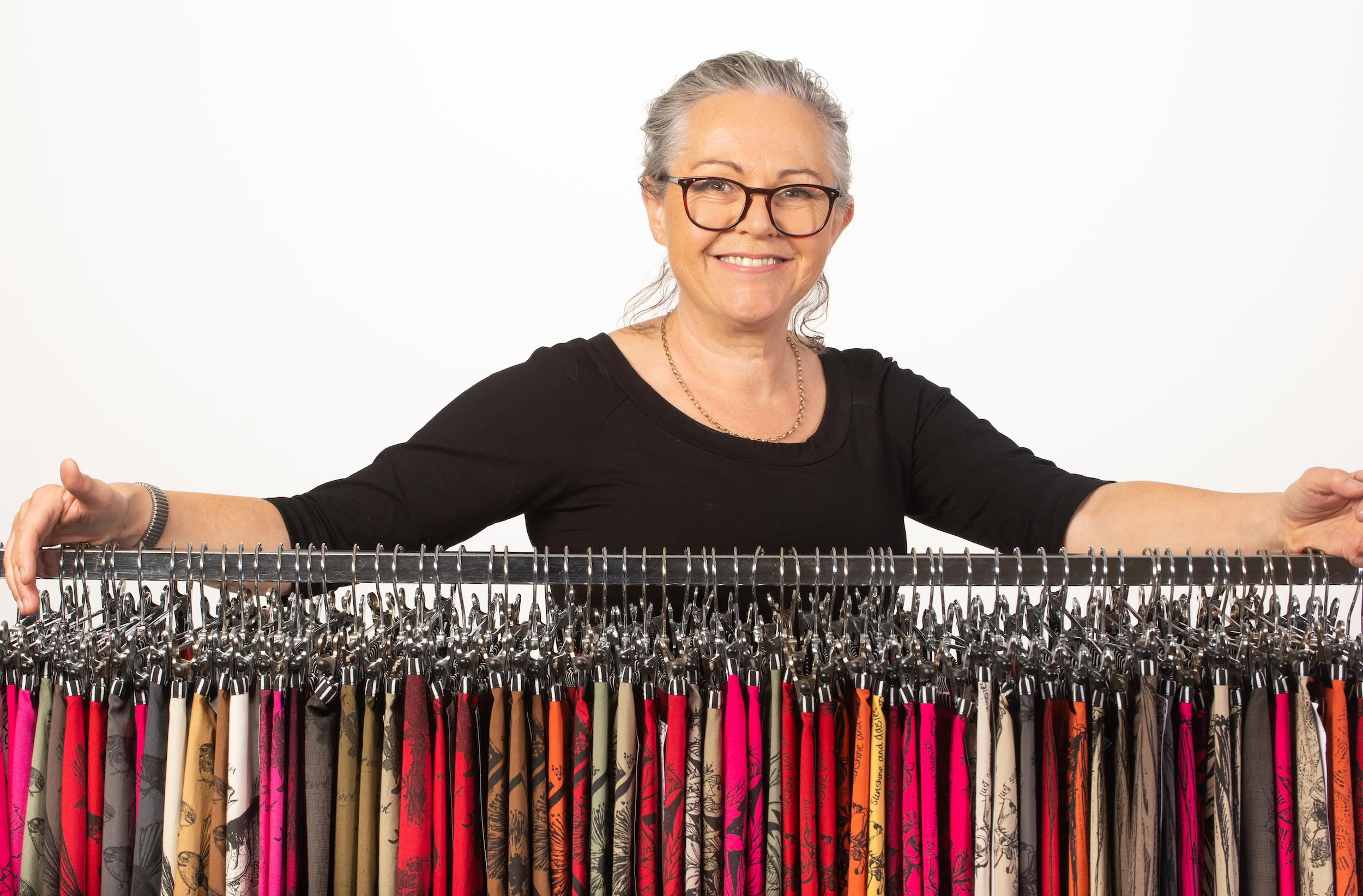 Image of Jill from Madcat Design standing with an selection of the skirts she makes